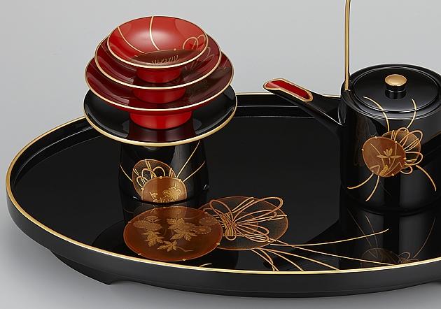 盃台には梅、銚子には蘭、屠蘇台には菊が、それぞれ鼓の中に描かれているのが見えます。 // 輪島塗 屠蘇器 小判形 鼓蒔絵 部分