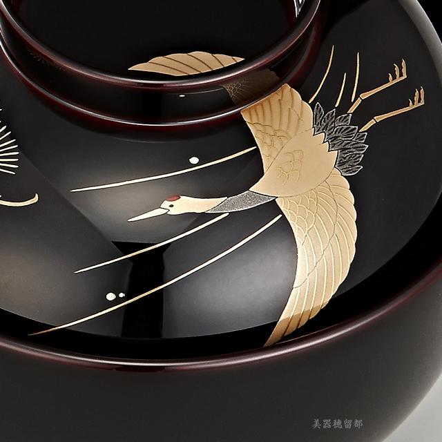 「輪島塗 雑煮椀 夫婦 溜塗 鶴亀松竹梅蒔絵」 鶴と松の蒔絵の椀(部分)<br><p>可愛らしさを感じさせる鶴。一枚一枚の羽にもご注目くださいね。</p>