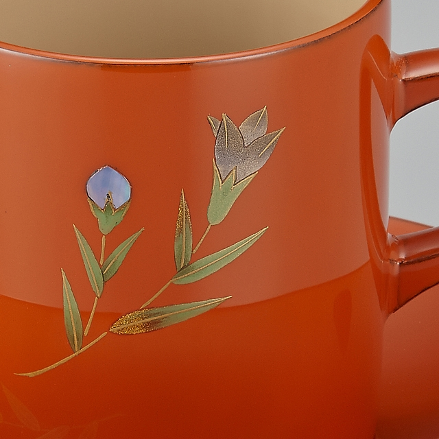 <p>カップに加色された竜胆(りんどう)の蒔絵です。// 輪島塗 コーヒーカップ りんどう蒔絵 外洗朱内白 (漆塗りスプーン付き) 蒔絵の部分画像</p>