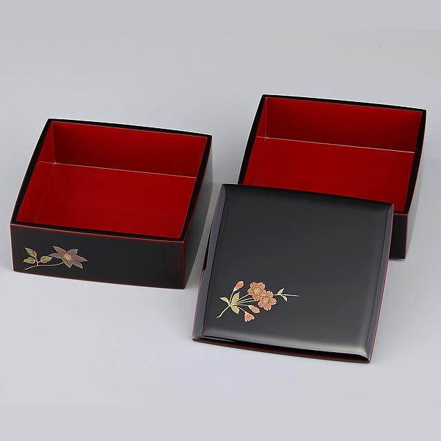 御重の蓋に描かれている桜と合わせて、5箇所に草花が描かれています。<br>重箱の外側が溜塗り(ためぬり)、内側が朱に塗られていますので「外溜内朱」と呼んでいます。<br>蒔絵が描かれている重箱の外側溜塗りの部分は「呂色仕上げ」、内側は「塗り立て」となります。<br>呂色仕上げは大変艶のある仕上がりです。呂色仕上げと比較すると「塗り立て」の艶はマットな感じになります。 // 輪島塗 重箱 小重二段 (5寸隅立胴張形) 外溜内朱 四季草花蒔絵